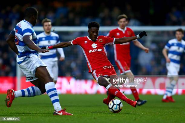 Ike Ugbo of MK Dons controls the ball under pressure from Nedum Onuoha of QPR during The Emirates FA Cup Third Round match between Queens Park...