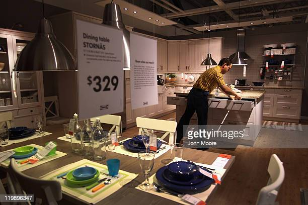 Ikea employee Joseph Roth adjusts a kitchen display ahead of the grand opening of the new Ikea home furnishings store on July 26 2011 in Centennial...