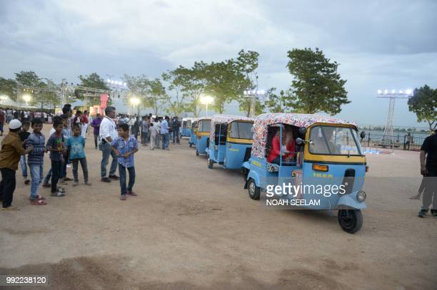 Ikea staff ride in auto rickshaws painted in Ikea colours at a promotional event for the new Ikea furniture store in Hyderabad on July 5 2018...