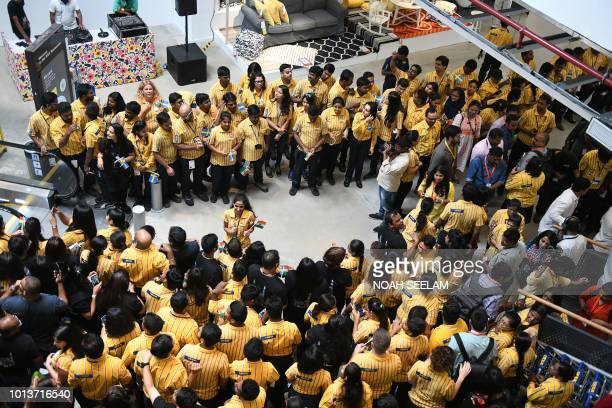 Ikea workers waits to welcome Indian customers at the entrance of the new IKEA store in Hyderabad on August 9 2018 Curious customers lay on beds and...