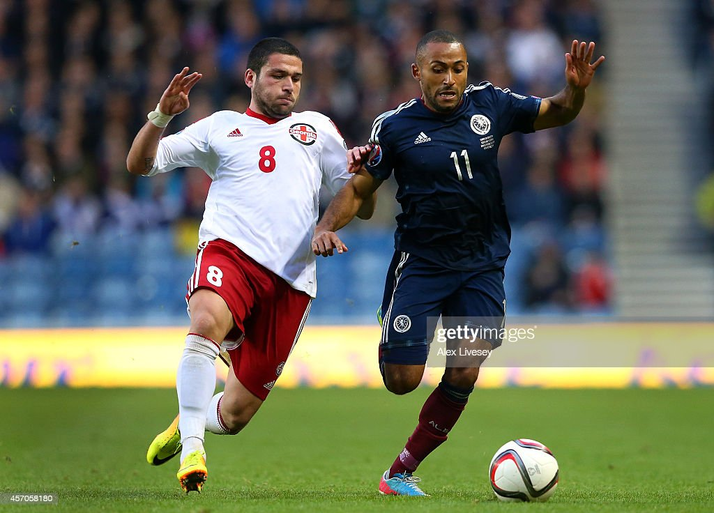 Ikechi Anya of Scotland is challenged by Murtaz Daushvili of Georgia during the EURO 2016 Qualifier match between Scotland and Georgia at Ibrox Stadium on October 11, 2014 in Glasgow, Scotland.