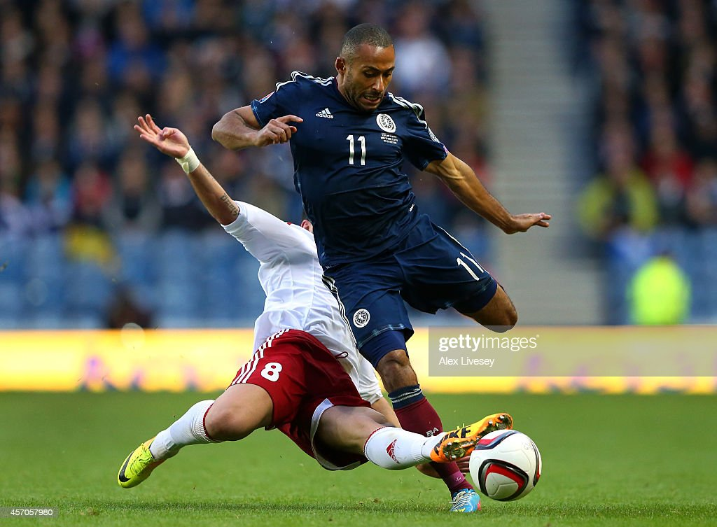 Ikechi Anya of Scotland is fouled by Murtaz Daushvili of Georgia during the EURO 2016 Qualifier match between Scotland and Georgia at Ibrox Stadium on October 11, 2014 in Glasgow, Scotland.