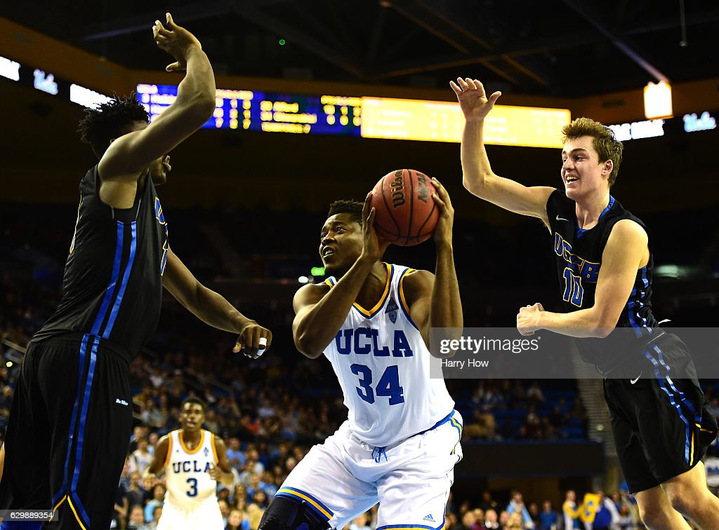 Ikenna Okwarabizie #34 of the UCLA Bruins makes a move between and Ami Lakoju #14 and Maxwell Kupchak #10 of the UC Santa Barbara Gauchos during a 102-62 win over the UC Santa Barbara Gauchos at Pauley Pavilion on December 14, 2016 in Los Angeles, California.