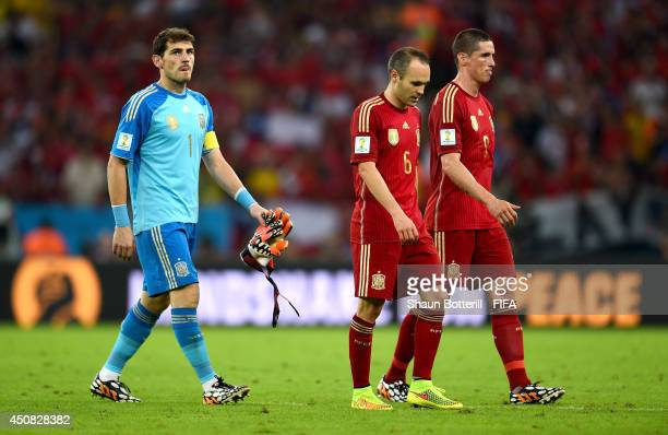 Iker Casillas Andres Iniesta and Fernando Torres of Spain walk off the pitch after the 2014 FIFA World Cup Brazil Group B match between Spain and...