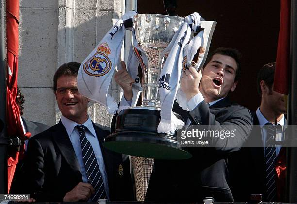 Iker Casillas of Real Madrid holds up the Trophy beside manager Fabio Capello of Italy a day after Real won their 30th Primera Liga at the Puerta del...