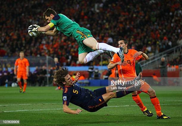 Iker Casillas of Spain catches the ball ahead of Robin Van Persie of the Netherlands as Carles Puyol of Spain falls to the ground during the 2010...
