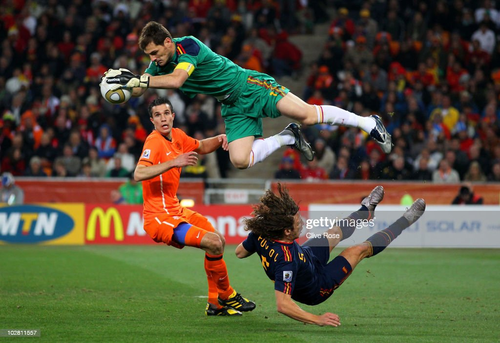 Iker Casillas of Spain catches the ball ahead of Robin Van Persie of the Netherlands as Carles Puyol of Spain falls to the ground during the 2010 FIFA World Cup South Africa Final match between Netherlands and Spain at Soccer City Stadium on July 11, 2010 in Johannesburg, South Africa.