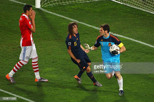 Iker Casillas of Spain celebrates with team mate Carles Puyol after saving the penalty kick from Oscar Cardozo of Paraguay during the 2010 FIFA World...