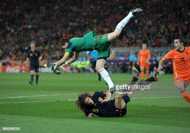 Iker Casillas of Spain collides with teammate Carlos Puyol as he collects the ball under pressure from Robin van Persie of the Netherlands during the...