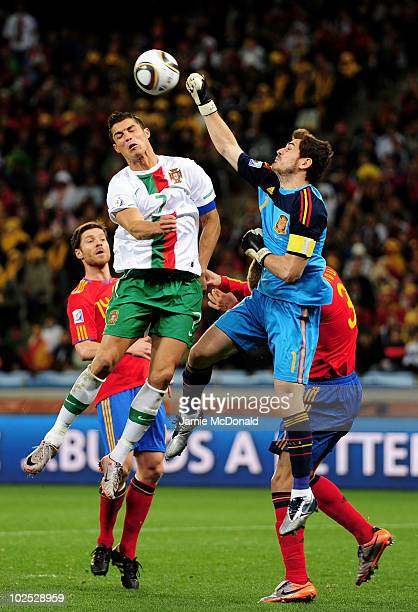 Iker Casillas of Spain defends an attack by Cristiano Ronaldo of Portugal during the 2010 FIFA World Cup South Africa Round of Sixteen match between...