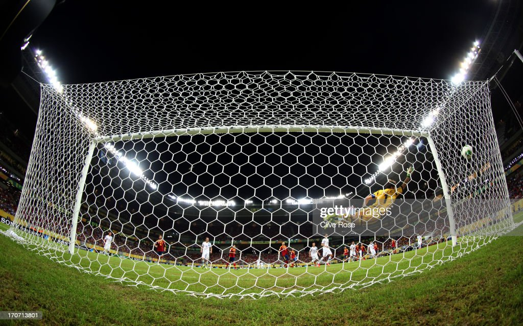 Iker Casillas of Spain is unable to stop Luis Suarez of Uruguay scoring his team's first goal from a free-kick during the FIFA Confederations Cup Brazil 2013 Group B match between Spain and Uruguay at the Arena Pernambuco on June 16, 2013 in Recife, Brazil.