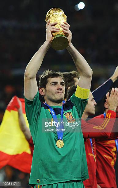 Iker Casillas of Spain lifts the World Cup trophy as the Spain team celebrate victory following the 2010 FIFA World Cup South Africa Final match...