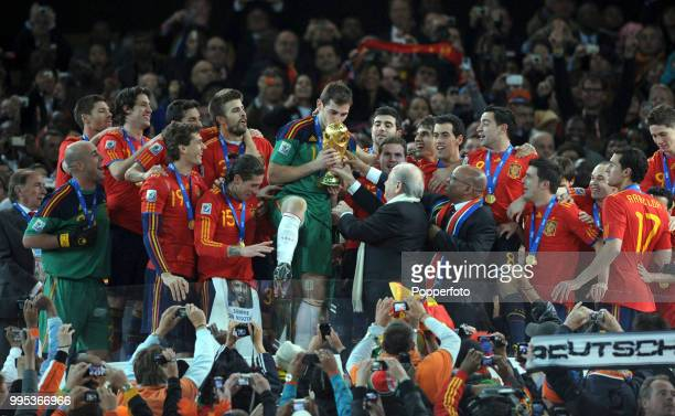 Iker Casillas of Spain receives the trophy from FIFA President Sepp Blatter after the FIFA World Cup Final between the Netherlands and Spain on July...