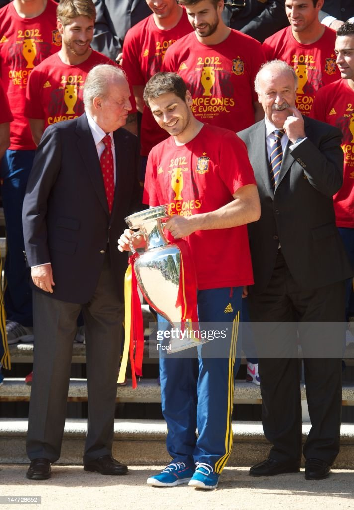 Iker Casillas (C) of Spain smiles holds the UEFA EURO 2012 trophy as he speaks with King Juan Carlos I of Spain (L) next to coach Vicente del Bosque at Zarzuela Palace on July 2, 2012 in Madrid, Spain.