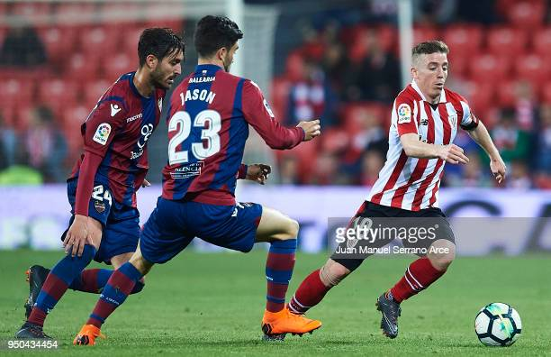 Iker Muniain of Athletic Club being followed by David Remeseiro 'Jason' of Levante UD and Jose Campana of Levante UD during the La Liga match between...