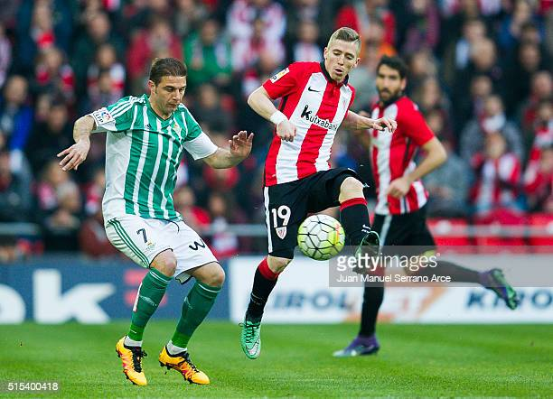 Iker Muniain of Athletic Club Bilbao competes for the ball with Joaquin of Real Betis Balompie during the La Liga match between Athletic Club Bilbao...