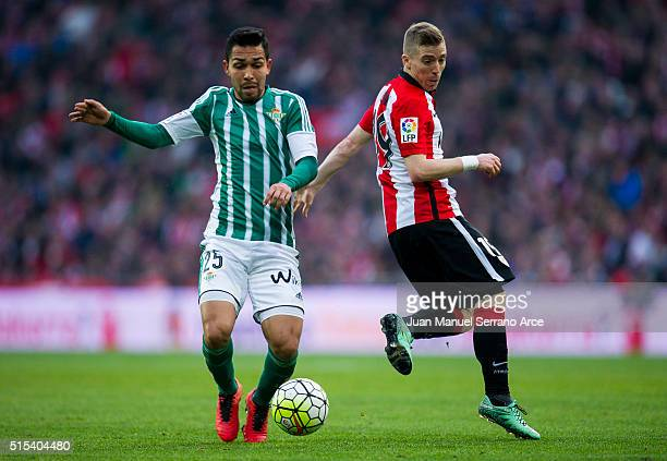 Iker Muniain of Athletic Club Bilbao competes for the ball with Petros of Real Betis Balompie during the La Liga match between Athletic Club Bilbao...