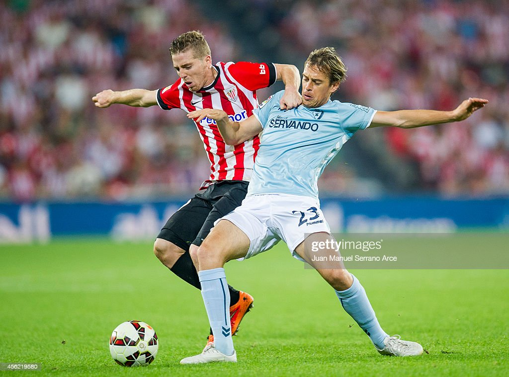 Iker Muniain of Athletic Club duels for the ball with Javier Lara of SD Eibar during the La Liga match between Athletic Club and SD Eibar at San Mames Stadium on September 27, 2014 in Bilbao, Spain.