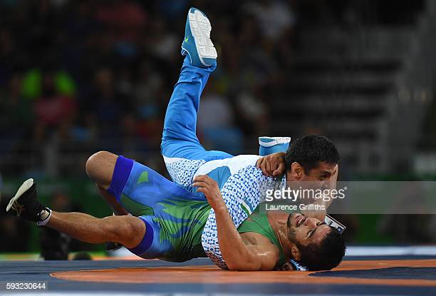 Ikhtiyor Navruzov of Uzbekistan and coach celebrate after winning the bronze in the Men's Freestyle 65kg Bronze match against Mandakhnaran Ganzorig...