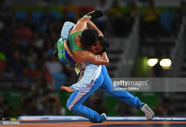 Ikhtiyor Navruzov of Uzbekistan and coach celebrate after winning the bronze in the Men's Freestyle 65kg Bronze match against Mandakhnaran Ganzorig...
