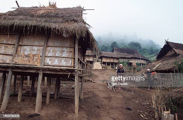 Iko villagers outside their bamboo huts in the village of Ban Long Muay a twoday walk from Muang Sing in Northern Laos The Iko people can be...