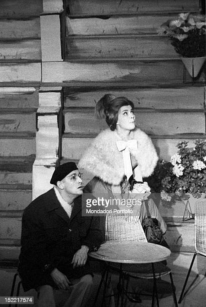 Ilaria Occhini standing and leanting on a chair with Vittorio Gassman sitting at a cafè table in a scene of 'Un marziano a Roma' Teatro Lirico Milan...