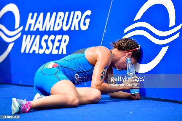 Ilaria Zane of Italy sits exhausted behind the finish line after completing in the Woman Elite sprint distance at the Hamburg Wasser ITU World...