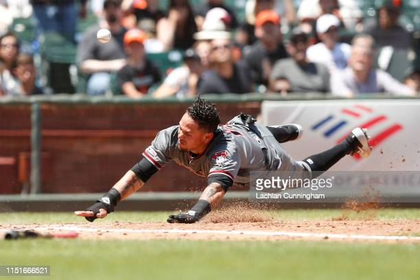 Ildemaro Vargas of the Arizona Diamondbacks slides into home plate to score in the top of the third inning against the San Francisco Giants at Oracle...