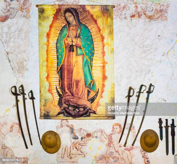 Ileana Sanchez house Mother Mary painting on cloth hanging on wall antique swords and shield beneath it on both sides Ileana Sanchez is a Cuban...