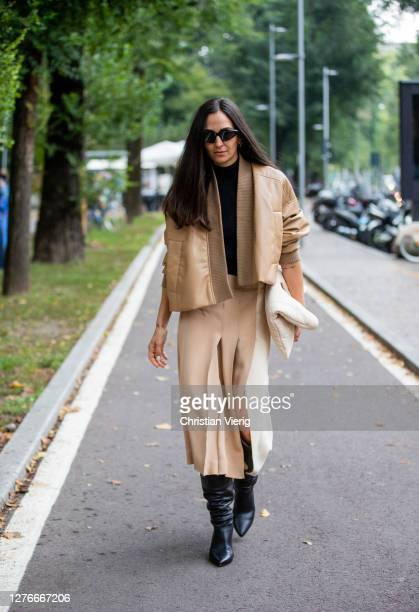 Ilenia Toma seen wearing beige jacket, skirt with slit, bag, black boots outside Sportmax during the Milan Women's Fashion Week on September 25, 2020...