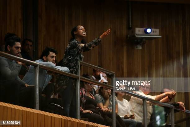 Ilham a resident who lost family members at the Grenfell disaster heckles from the public gallery during a Kensington Council meeting to discuss...