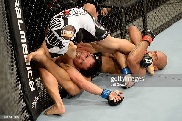Iliarde Santos attempts a submission against Chris Cariaso in their flyweight bout during the UFC Fight Night event at the Ginasio Jose Correa on...