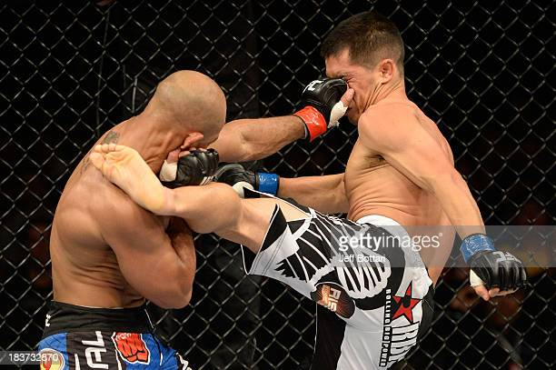 Iliarde Santos punches Chris Cariaso in their flyweight bout during the UFC Fight Night event at the Ginasio Jose Correa on October 9, 2013 in...