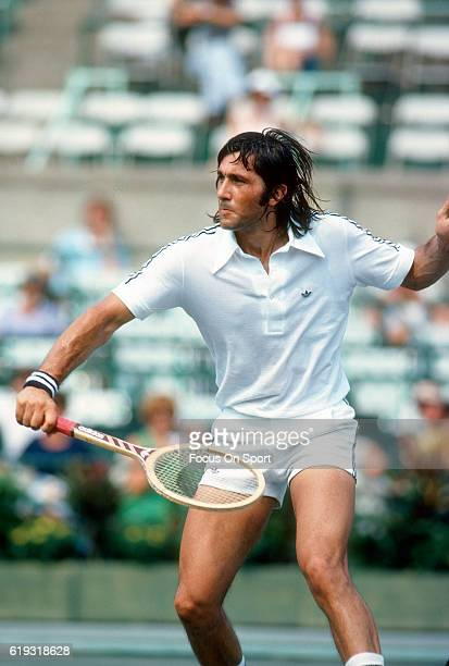 Ilie Nastase of Romania hits a return during a match in the Men's 1977 US Open Tennis Championships circa 1977 at the West Side Tennis Club in the...