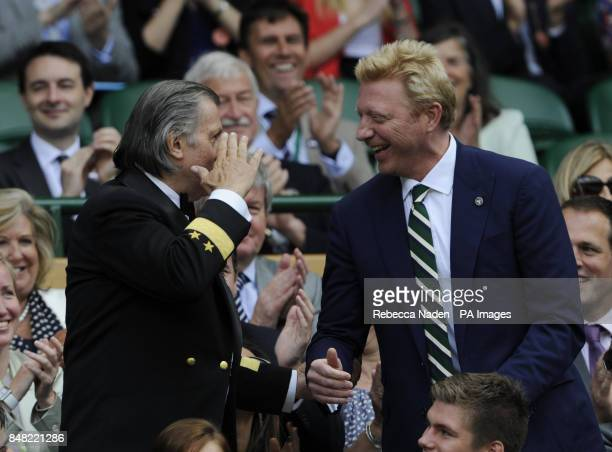 Ilie Nastase salutes Boris Becker in the Royal Box during day six of the 2012 Wimbledon Championships at the All England Lawn Tennis Club Wimbledon