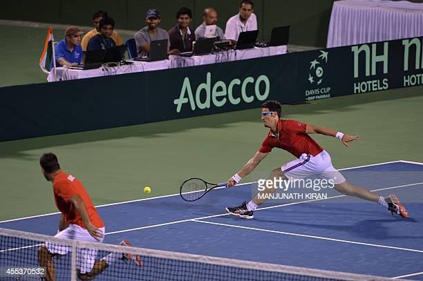 Ilija Bozoljac of Serbia plays a shot as his partner Ninad Zimonjic looks on during the men's doubles match against Leander Paes and Rohan Bopanna of...