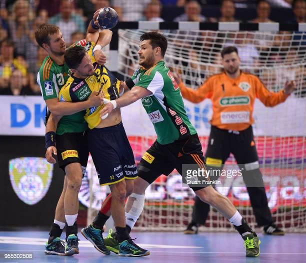 Ilija Brozovi and Evgeni Pevnov of Hannover challenge Alexander Petersson of RheinNeckar during the final of the DKB Handball Bundesliga Final Four...