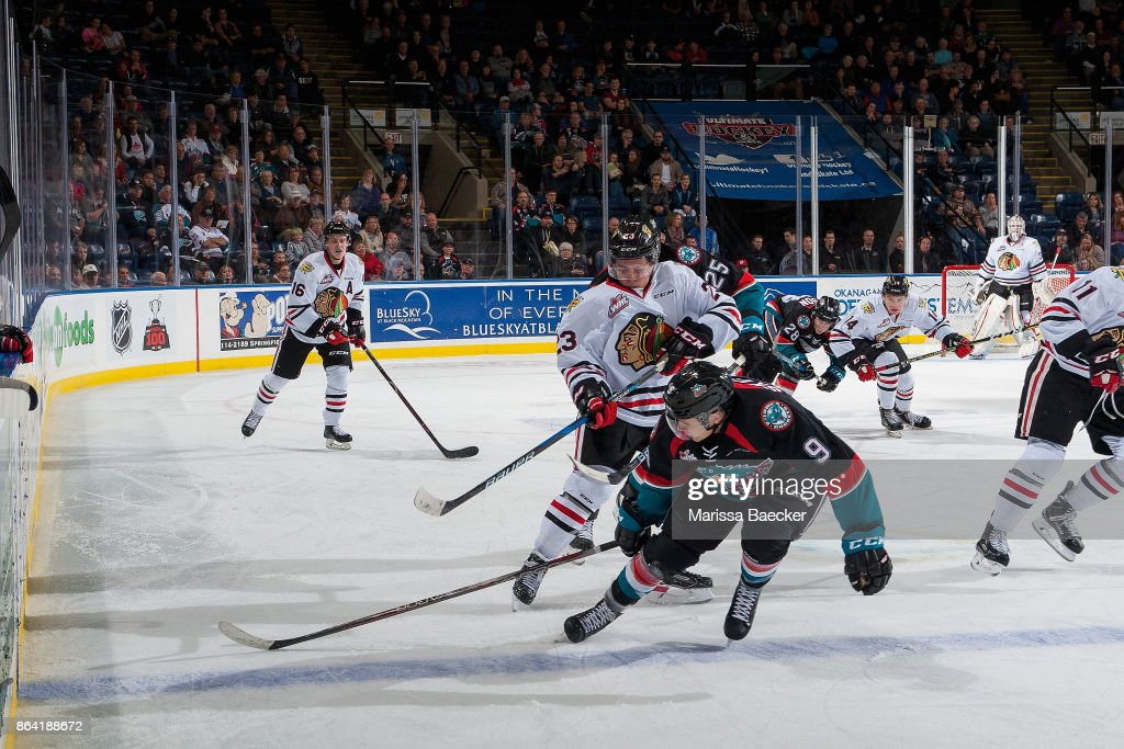 Ilijah Colina #23 of the Portland Winterhawks shoots the puck into the boards as Marek Skvrne #9 of the Kelowna Rockets tries to block the pass during third period at Prospera Place on October 20, 2017 in Kelowna, Canada.
