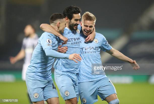 Ilkay Guendogan of Manchester City celebrates with Oleksandr Zinchenko and Phil Foden after scoring their team's first goal during the Premier League...
