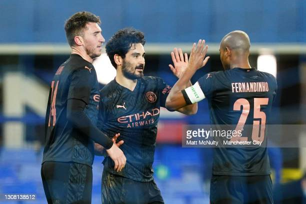Ilkay Guendogan of Manchester City celebrates with team mates Aymearic Laporte and Fernandinho after scoring their side's first goal during The...