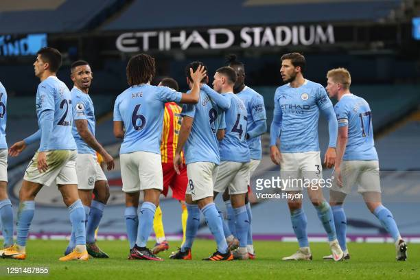 Ilkay Guendogan of Manchester City is congratulated by Nathan Ake and Phil Foden after scoring their team's first goal during the Premier League...