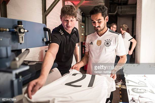 Ilkay Guendogan prints his name and number on a jersey during the ADIDAS presentation of the new DFB home jersey for the FIFA Confederations Cup at...