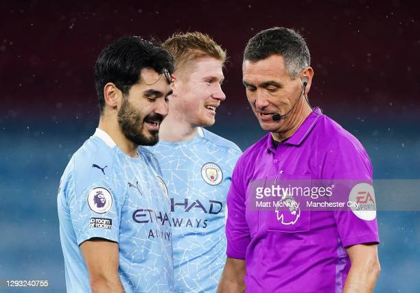 Ilkay Gundogan and Kevin de Bruyne of Manchester City share a joke with referee Andre Marriner during the Premier League match between Manchester...