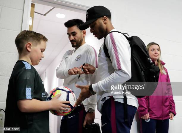 Ilkay Gundogan and Raheem Sterling of Manchester City sign an autograph as they arrive prior to the Carabao Cup semifinal second leg match between...