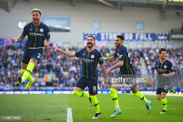 Ilkay Gundogan celebrates with Kyle Walker and Riyad Mahrez after scoring a goal during the Premier League match between Brighton Hove Albion and...