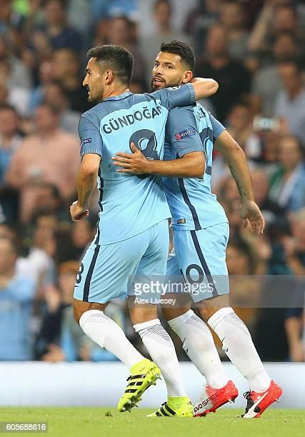 Ilkay Gundogan congratulates Sergio Aguero of Manchester City after scoring his teams opener during the UEFA Champions League match between...