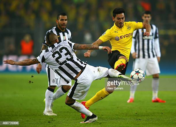 Ilkay Gundogan of Borussia Dortmund is tackled by Arturo Vidal of Juventus during the UEFA Champions League Round of 16 between Borussia Dortmund and...