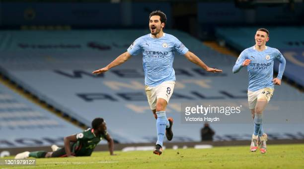 Ilkay Gundogan of Manchester City celebrates after scoring their side's third goal as team mate Phil Foden comes to congratulate during the Premier...