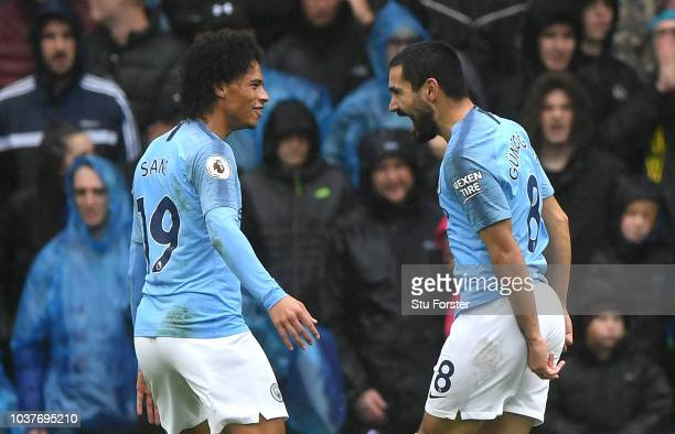 Ilkay Gundogan of Manchester City celebrates with teammate Leroy Sane after scoring his team's third goal during the Premier League match between...