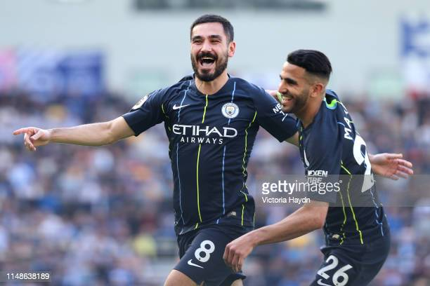 Ilkay Gundogan of Manchester City celebrates with teammate Riyad Mahrez after scoring his team's fourth goal during the Premier League match between...